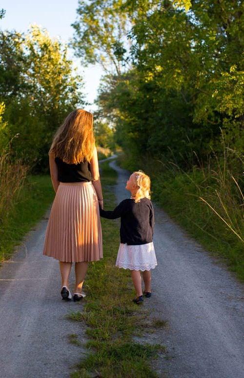 Woman and girl walking down path