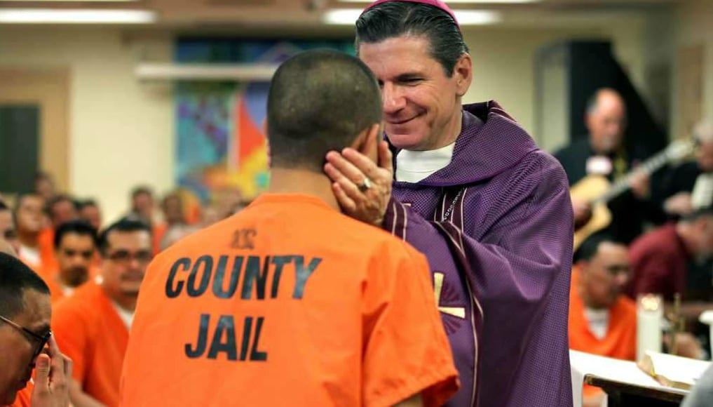 bishop gustavo smiles at prisoner