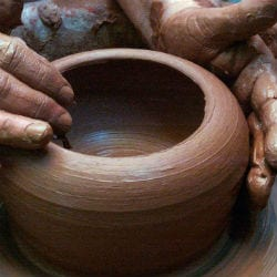 potter forming a clay pot with hands dirty