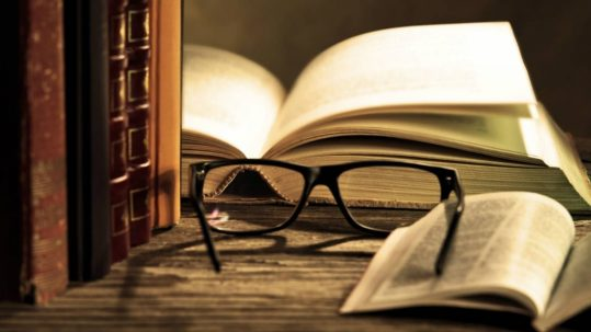 glasses on table next to books
