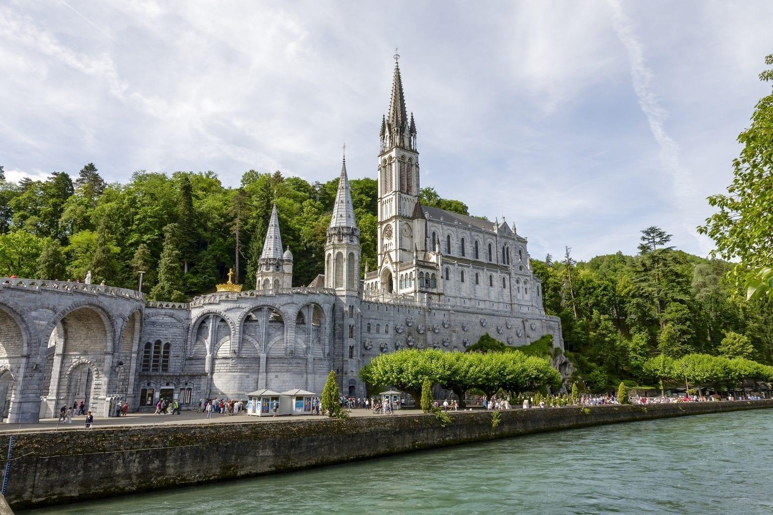 The Basilica of Lourdes at Gave de Pau river - Crossroads Initiative